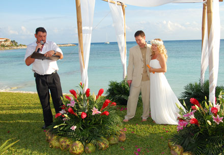 Minister talking to the bride and groom in the beach